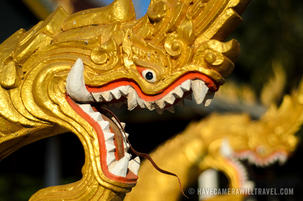 Intricately carved and brightly decorated dragons on the outside of a Wat (Buddhist Temple) in Vientiane, Laos.