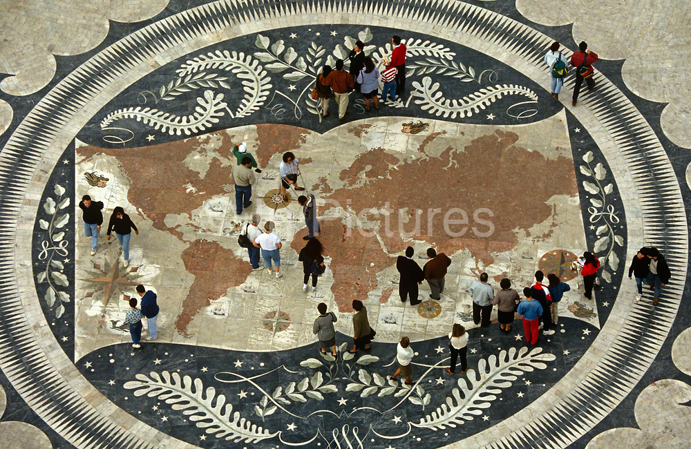 Portuguese pedestrians walk over a world map on the pavement beneath the Monument of Discoveries, Lisbon. The world's landmass is represented here in a tiled mosaic that Portugal is famous for and citizens walk across this depiction of their planet like giants on a mini-sized map. Located in Belém, on the bank of the River Tagus where the monument celebrates an era of adventure, expansion and colonial ambition. Within a circular frame, the ornate map shows an almost ancient world minus its geopolitical borders.