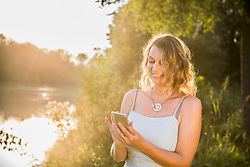 Cheerful woman smiling while using smart phone at riverbank, Bavaria, Germany