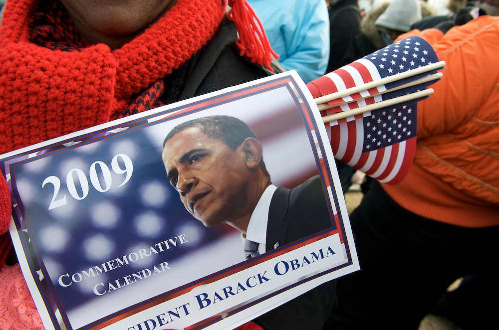 Clutching a flag and calender, a Barack Obama expresses her patriotism on the day of Barack Obama's historic Presidential inauguration.  An estimated two million people flocked to Washington D.C. for the ceremony, enduring freezing temperatures to witness Obama take the oath of office becoming the first African-American to become President, the 44th in the history of the United States of America.