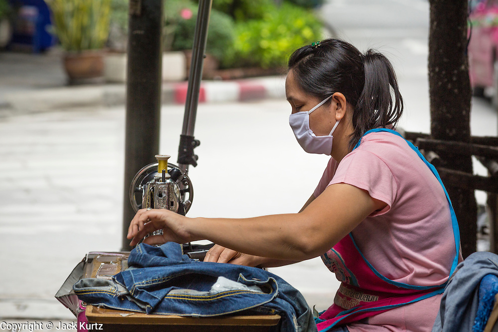 """24 AUGUST 2013 - BANGKOK, THAILAND: A seamstress works on a street in Bangkok. Workers in the informal economy have not been impacted by the recession yet but more and more people are joining the informal economy. Thailand entered a """"technical"""" recession this month after the economy shrank by 0.3% in the second quarter of the year. The 0.3% contraction in gross domestic product between April and June followed a previous fall of 1.7% during the first quarter of 2013. The contraction is being blamed on a drop in demand for exports, a drop in domestic demand and a loss of consumer confidence. At the same time, the value of the Thai Baht against the US Dollar has dropped significantly, from a high of about 28Baht to $1 in April to 32THB to 1USD in August.     PHOTO BY JACK KURTZ"""