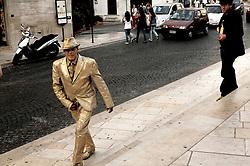 Un artista di strada al termine della pausa si dirige verso la sua postazione di lavoro, dopo aver parlato col suo collega.