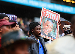 Mandela Memorial Service.<br /> 60813445 <br /> A man holding a poster of Nelson Mandela before the memorial service for the former South African president at the FNB Stadium in Soweto near Johannesburg, South Africa, Tuesday, 10th December 2013. Picture by  imago / i-Images<br /> <br /> UK ONLY