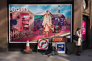 Lady smoker and roadworks signs below an Oasis fashion poster featuring a young woman in a utopian fantasy about to cross a road. Stopping for a smoke before carrying on her journey, the scene behind her is of a scene of retail paradise that features the model wheeling a shopping trolley, we also see a dystopian reality of the everyday city, the abandoned traffic signs leaning against this poster for the womens' retailer Oasis. A No Right-Turn and a Priority sign have been left on the ground, perfectly in context with the message above.