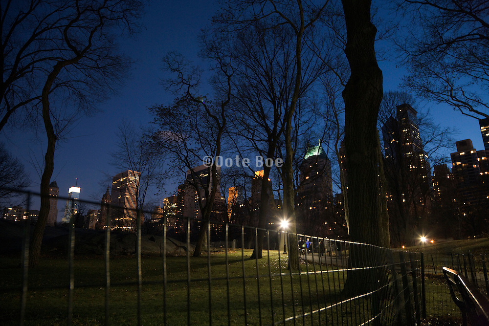 Central park in New York City at dusk with West 59th street high rise in the back ground