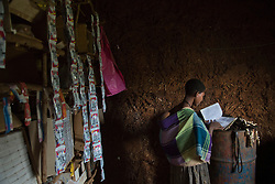 """Destaye, 15, looks through her old schoolbooks in the store she and her husband Addisu, 27, run out of their home near Bahir Dar, Ethiopia on Aug.13, 2012. At the time of their marriage, when Destaye was age 11, she was still in school and her husband expressed interest in letting her continue her education. Destaye, despite teasing from her community, intended to stay in school. """"They used to laugh at me for going to school after marriage,"""" she said. """"But I know the use of school so I don't care...But people laughing at you makes it more difficult.""""  After the birth of her son six-months ago, however, Destaye no longer had time for classes. """"I feel sad because I quit learning,"""" she said."""