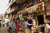 Copper pot merchant in a busy street in Kathmandu's old town attends to his wares as people walk by.