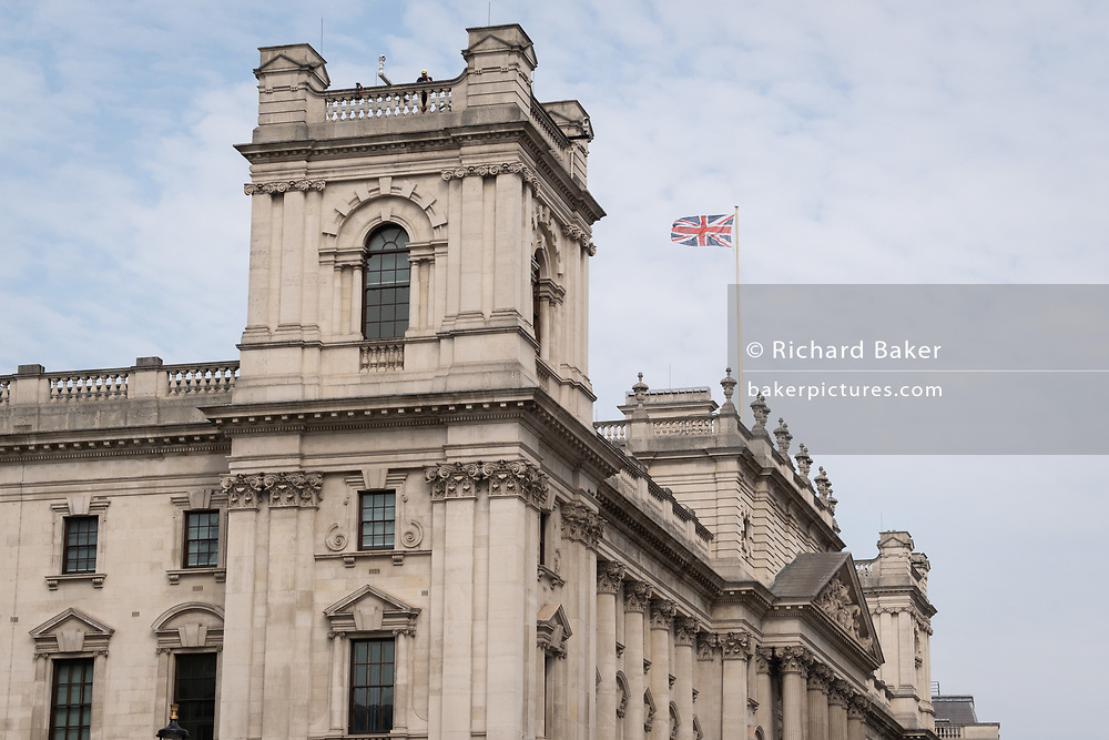 As a police officer watches a small protest in Parliament Square, the Union Jack flies over the Treasury in Whitehall, the location for many British government buildings in Westminster, on 16th September 2020, in London, England.