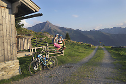 Young couple of mountain bikers sitting on wooden fence, Zillertal, Tyrol, Austria