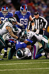 New York Giants quarterback Eli Manning #10 is sacked by Philadelphia Eagles defensemen during the NFL game between the Philadelphia Eagles and the New York Giants on December 13th 2009. The Eagles won 45-38 at Giants Stadium in East Rutherford, New Jersey. (Photo By Brian Garfinkel)