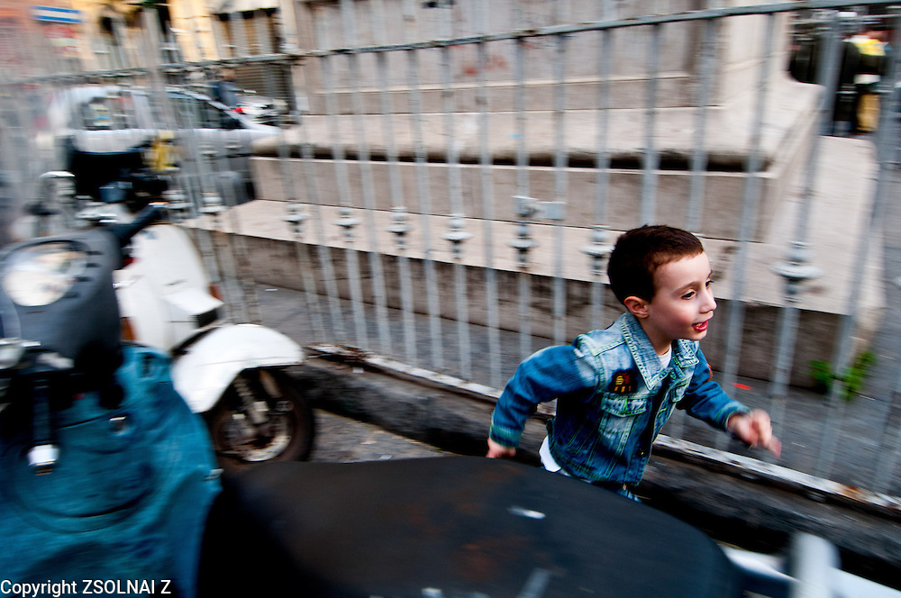 A kid is palying in the streets of Naples, trying to escape from their from his chasers. Naples, Italy.