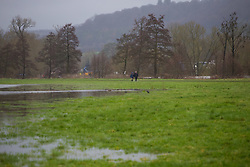 A distant couple walk between the River Thames and a flooded meadow at Aston near Henly as heavy rains in the catchment area and saturated ground cause the river to rise to within inches of bursting its banks.. April 02 2018.