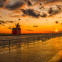 The sun sets over Lake Michigan and the Big Red Lighthouse in Holland, Michigan