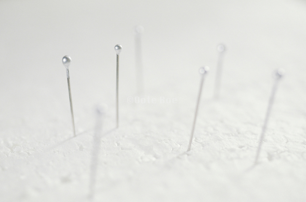 sewing pins stuck in white styrofoam