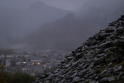 A mountain of slate waste is seen above the town of Blaenau Ffestiniog, on 2nd October 2021, in Blaenau Ffestiniog, Gwynedd, Wales. The derelict slate mines around Blaenau Ffestiniog in north Wales were awarded UNESCO World Heritage status in 2021. The industry's heyday was the 1890s when the Welsh slate industry employed approximately 17,000 workers, producing almost 500,000 tonnes of slate a year, around a third of all roofing slate used in the world in the late 19th century. Only 10% of slate was ever of good enough quality and the surrounding mountains now have slate waste and the ruined remains of machinery, workshops and shelters have changed the landscape for square miles.