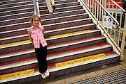 Child (6 years old) standing on stairs at railway station. Sydney, Australia