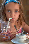 Young girl of six enjoying her milkshake in an outdoor cafe - model release available