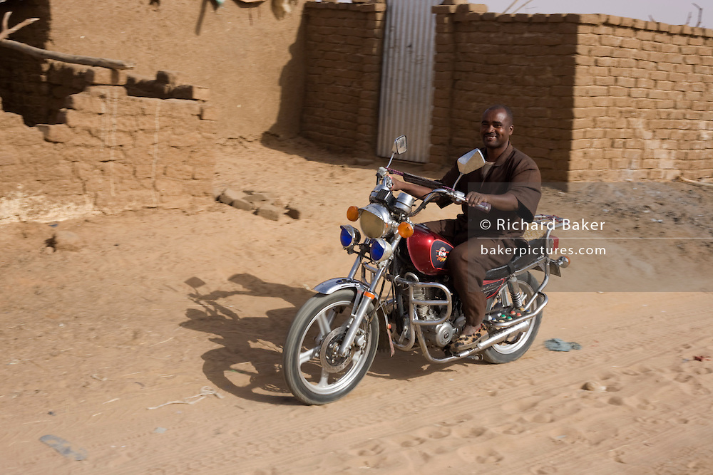 Man on a smart motorbike smiles as he rides past the viewer in the 4 sq km Abu Shouk refugee camp which is (disputedly) home to 38,000 displaced persons and families on the outskirts of the front-line town of Al Fasher (also spelled, Al-Fashir) in north Darfur. .