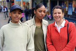 Single mother standing in town centre with teenage daughter and son,