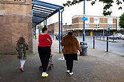 Young family walking past a small shopping area, most of which is closed down in Highgate, the inner city area of Birmingham which is virtually deserted under Coronavirus lockdown on 29th April 2020 in Birmingham, England, United Kingdom. Coronavirus or Covid-19 is a new respiratory illness that has not previously been seen in humans. While much or Europe has been placed into lockdown, the UK government has put in place more stringent rules as part of their long term strategy, and in particular social distancing.