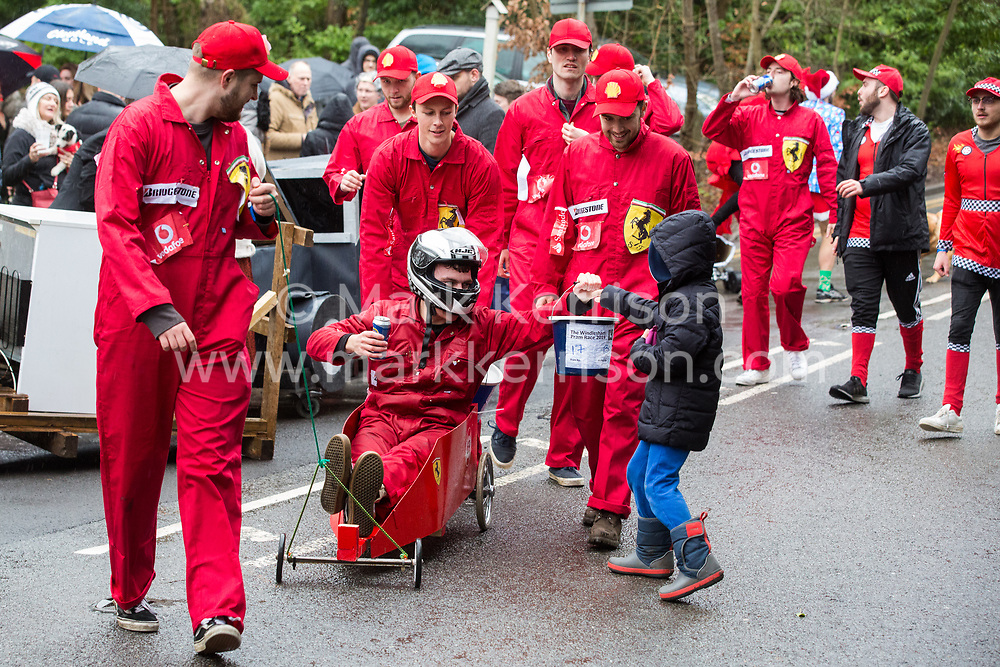 Windlesham, UK. 26 December, 2019. A child makes a contribution to competitors taking part in the annual fancy dress Windlesham Boxing Day Pram Race charity event along a 3.5-mile course through Windlesham village with stops at local pubs along the route.