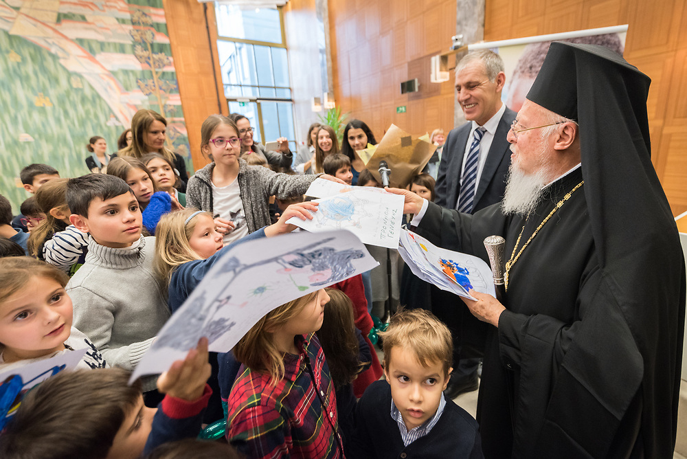 """21 November 2018, Geneva, Switzerland: Children from the Greek schools in Geneva and Lausanne hand over drawings to the Ecumenical Patriarch Bartholomew as a friendly gesture of welcome, as he arrives at the Ecumenical Centre. On the occasion of 2018 World Children's Day, and in recognition of the World Council of Churches' 70th anniversary, UNICEF and WCC convene a number of WCC member churches and common partners to celebrate the UNICEF-WCC global partnership and to take stock of the many achievements of the Churches' Commitments to Children. In line with the spirit of a day """"for children, by children,"""" the celebratory event placed children at the centre by asking them to share their recent experiences as participants in the several Youth Talks on ending violence in schools that WCC member churches around the world have organized in recent years; hearing the perspective of young migrants supported by a church-run sponsorship project; and showcasing promising examples of how churches support children in climate justice activities."""