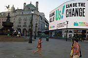 With a further 149 reported dying from Coronavirus in the last 24hrs, taking the UK death toll to 43,320, shoppers walk past digital advertising and the statue of Eros in Piccadilly Circus during the Covid pandemic, on 25th June 2020, in London, England.