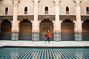 A female tourist walks alone across the inner courtyard in the Ali ben Youssef Medersa in the Marrakech medina, Morocco on November 16, 2007.