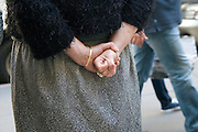 middle aged woman holding hand in a fist behind her back