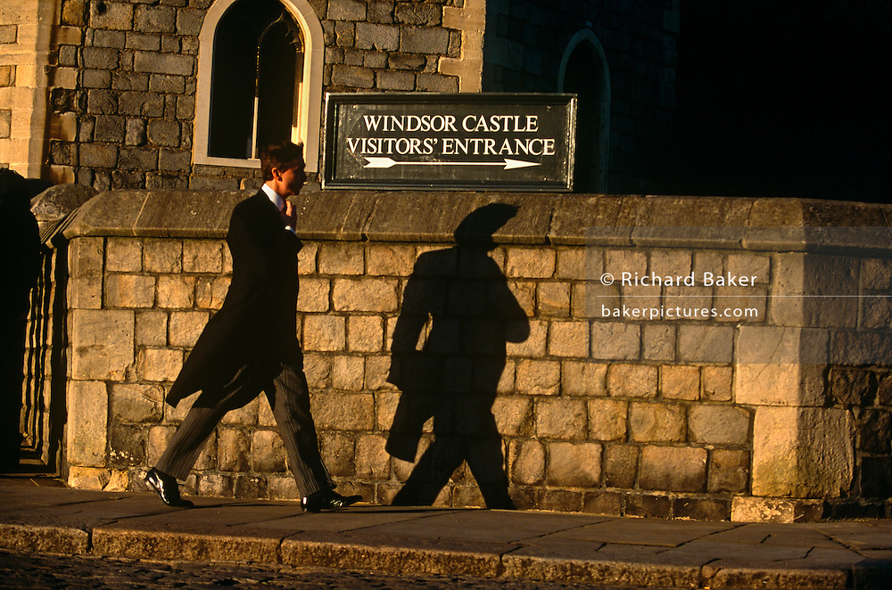 A mourner in tailed jacket and pinstripes, walks towards Windsor Castle's visitor entrance for Princess Margaret's funeral.