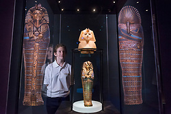 """© Licensed to London News Pictures. 01/11/2019. LONDON, UK. A staff member views """"Calcite Stopper for Canopic Jar, King's Head: NW"""" and """"Gold Inlaid Canopic Coffinette of Tutankhamun Dedicated to Imseti and Isis"""".  Preview of """"Tutankhamun, Treasures of the Golden Pharoah"""" at the Saatchi Gallery in Chelsea.  The exhibition celebrates the 100th year anniversary of the opening of Tutankhamun's tomb and displays 150 works in the largest collection of Tutankhamun's treasures ever to leave Egypt.  The show runs 2 November to 3 May 2020.  Photo credit: Stephen Chung/LNP"""