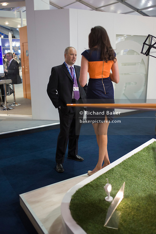 Delegate chats to a leggy trade stand woman at the Farnborough Air Show, UK.