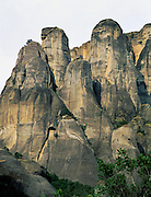 """Fantastic rock spires of Meteora rise above Kastraki, near Kalambaka, in central Greece, Europe. Meteora (which means """"suspended in the air"""") is a complex of six Eastern Orthodox Christian monasteries built by medieval monks on natural rock pillars. The sandstone and conglomerate of Meteora were formed in the cone of a river delta estuary emerging into a sea about 60 million years ago, then later uplifted and eroded into pinnacles. The isolated monasteries of Meteora helped keep alive Greek Orthodox religious traditions and Hellenic culture during the turbulent Middle Ages and Ottoman Turk occupation of Greece (1453-1829). UNESCO honored Meteora as a World Heritage Site in 1988. Visit early in the morning and in the off season to avoid crowds."""