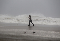 A man walks along the beach, defying the strong winds near to the city pier early morning in Panama City Beach, as Florida's Panhandle prepares for its worst hurricane strike in at least a decade as Michael gained power overnight, on track to strike somewhere near Panama City Wednesday afternoon, Oct. 10, 2018. Photo by Pedro Portal/Miami Herald/TNS/ABACAPRESS.COM