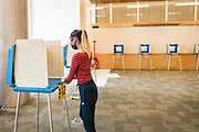 An election volunteer disinfects the voting booth at a polling location in Downtown Minneapolis, Minnesota, U.S., on Tuesday, Aug. 11, 2020. Photographer: Ben Brewer/Bloomberg