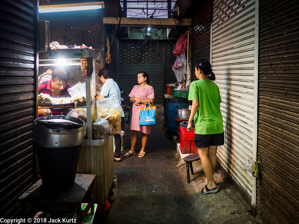 23 FEBRUARY 2018 - BANGKOK, THAILAND: People at a soup stall in Pratunam Market with a construction fence in the background. Photos of Thai royalty are on the fence. Pratunam Market was one of the largest clothing markets in Bangkok. New airconditioned markets, like Platinum and Palladium malls opened nearby, siphoning away customers. Now there are only a handful of merchants left in the market and Bangkok city officials have plans to shut the market and redevelop the land.      PHOTO BY JACK KURTZ