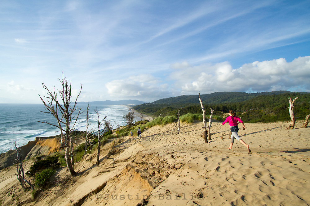 Family playing on sand dunes in Pacific City, OR