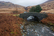 A now disused stone bridge (only used by grazing cattle) and winter bracken over the Coladoir River on Glen More, Isle of Mull, Scotland. The wide landscape view shows us the bridge's strength largely given by the beautiful workmanship by those using local materials for this road overpass. Only farm vehicles and small cars generally drive over but such structures need to withstand harsh winters where weather can help them deteriorate. An arch is a structure that spans a space and supports a load. Arches appeared as early as the 2nd millennium BC in Mesopotamian brick architecture and their systematic use started with the Ancient Romans who were the first to apply the technique to a wide range of structures.