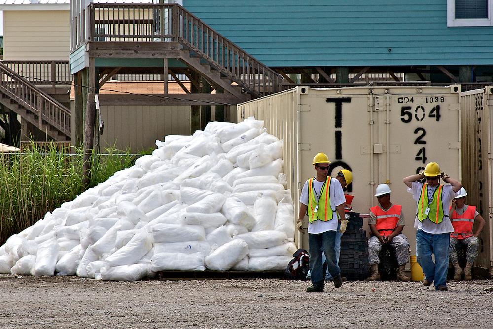 Relief workers rest near oil boom at Shell Beach, St. Bernard Parish, Louisiana