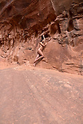 Nude woman posing in a slot canyon near Moab, Utah