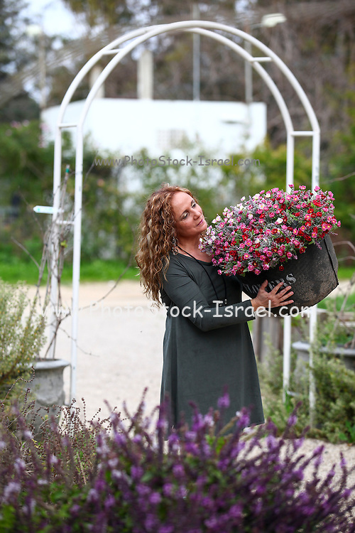Woman admires the flowers in her garden