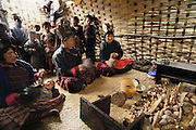 Inside a makeshift tent outside the Shingkhey Buddhist Temple, a two-day ceremony is held to bless the village. To a continuous background of chanting, the monks fill the valley with long, slow, deep notes from their horns. Bhutan. From Peter Menzel's Material World Project.
