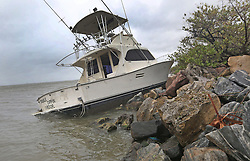 October 7, 2016 - Tallahassee, FL, USA - A cabin cruiser that probably had broken loose from its moorings sits among the rocks Thursday, October 7, 2016  along the Banana River.  Hurricane Matthew a Category 4 storm brushed the Florida east coast. (Credit Image: © Red Huber/TNS via ZUMA Wire)