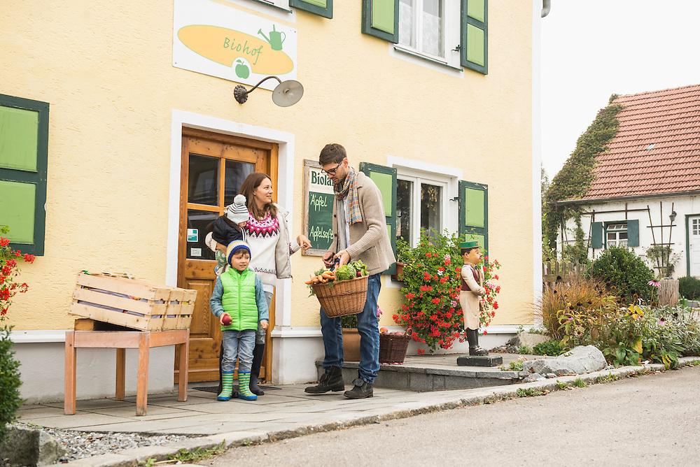 Nuclear family standing in  an organic farm and smiling, Bavaria, Germany