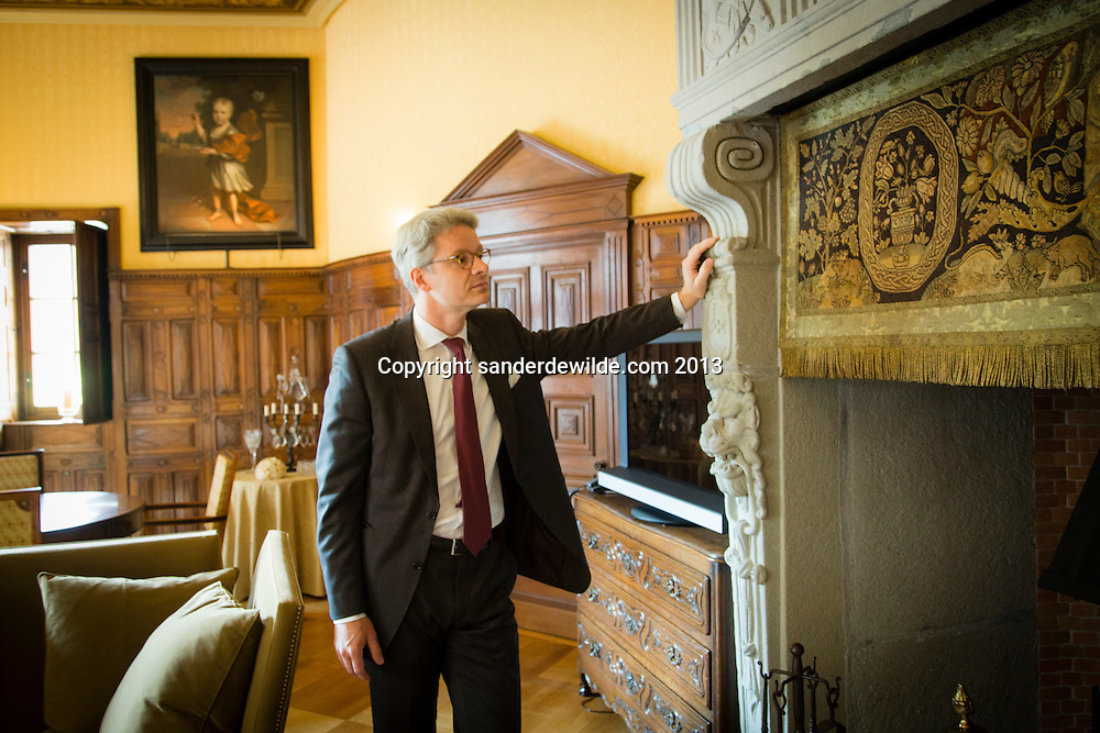 Interior architectThierry THENAERS leaning on a medieval fireplace in one of the rooms of Chateau d'Anthée, having been totally renovated by him. The tapestry above the fireplace (right) is original. Credit Sander de Wilde for The Wall Street Journal.  Castle