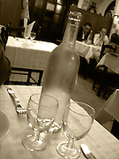 restaurant in europe.interior close up of water bottle wine galsses on table with tables in background,sepia,verticle