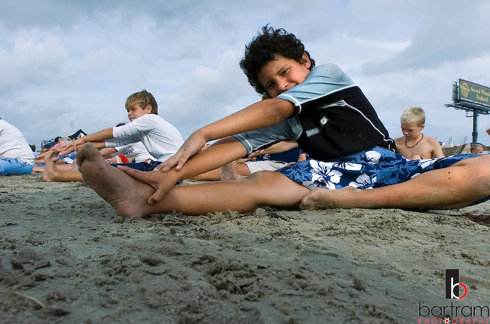 KEVIN BARTRAM/The Daily News.Jesse Zapata, 9, stretches before the start of the Ohana Surf Camp on the beach near 28th Street and Seawall Boulevard on Tuesday, July 19, 2005. The camp for surfers 6-17 years old has another session planned for August 2-4. There is also a girls only session planned for September 10-11.