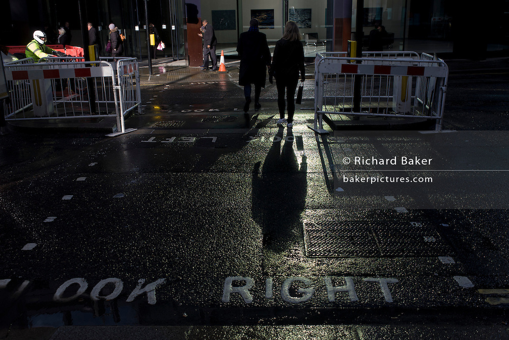 In strong sunlight, pedestrians in the financial City of London's Threadneedle Street cross the road in front of traffic still wet after recent showers.