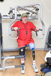 Man with prosthetic limb using the chest press at a gym,