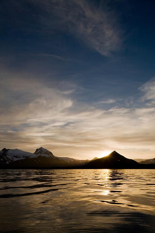 USA, Alaska, Katmai National Park, Setting sun lights clouds above mountain peaks lining Hallo Bay on summer evening